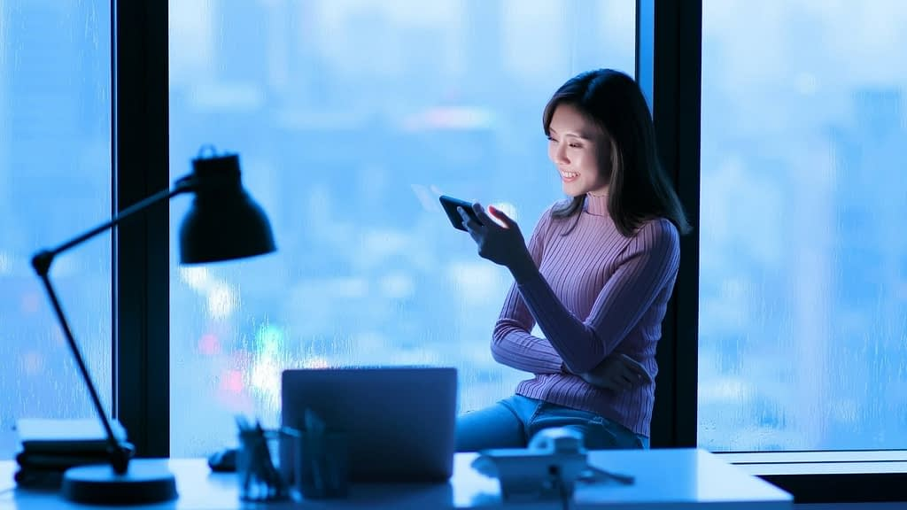 woman is watching a video on her mobile device and she is smiling
