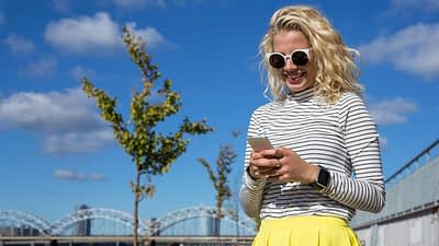 A blond woman is standing outside by the trees and a couple of bridges. She's wearing a yellow skirt, apple watch, and striped turltle neck top and glasses. She is chatting over text.