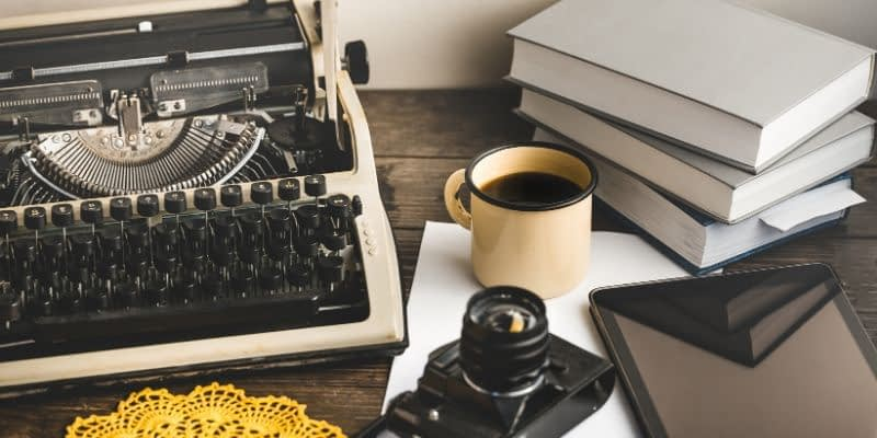 Desk with coffee, typewriter, books, camera, looks like someone is writing a book