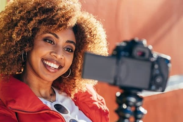 Pretty woman is standing in front of video camera making videos for Youtube