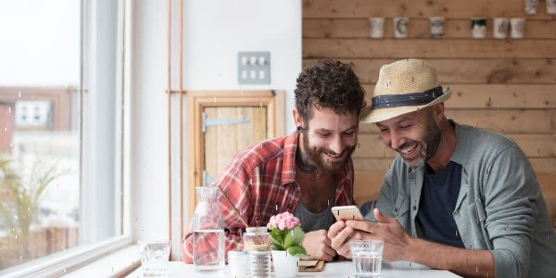 2 Men are looking at mobile phone content and smiling.