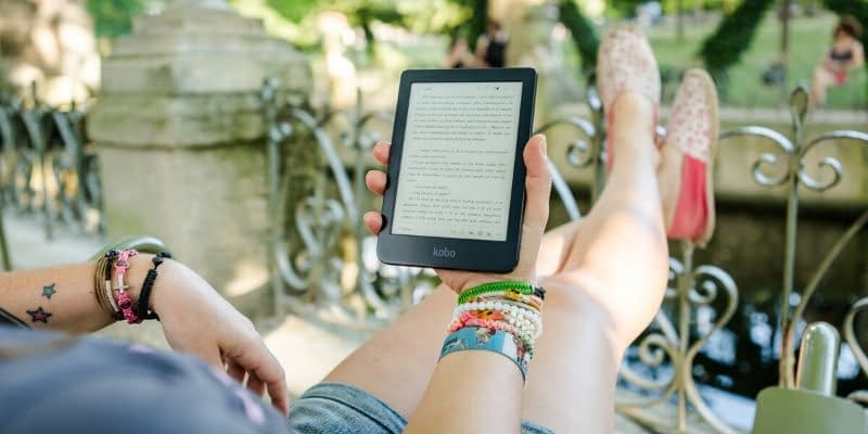 Girl is kicking back with an ebook on a tablet or kindle ebook reader