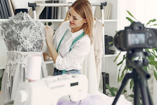 Woman is in a fashion design studio making a video for youtube