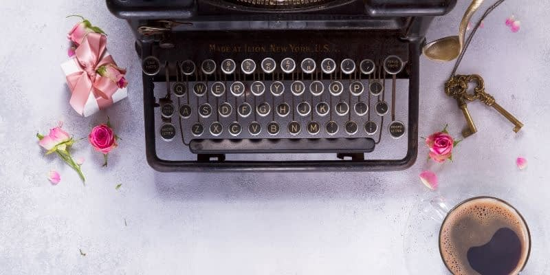 Old time typerwriter ready for someone to write, nearby cup of coffee