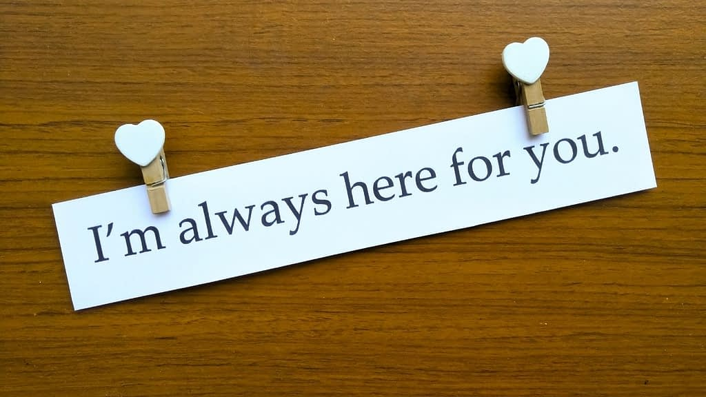 The sentence I'm always here for you is pinned up with heart paper clips or pins