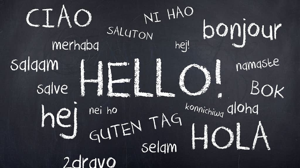 """Multiple Languages are saying """"hello"""" on a chalk board"""