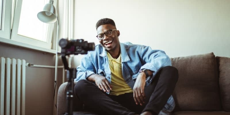 Young man is smiling in front a video camera getting ready to run a Youtube ad