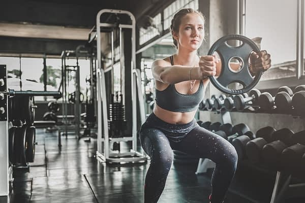 a strong young woman in a french braid and fitness clothes is squatting while holding a weight