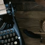 Antique desk with old typerwriter and plume in sepia - looks haunted to imply a ghostwriter
