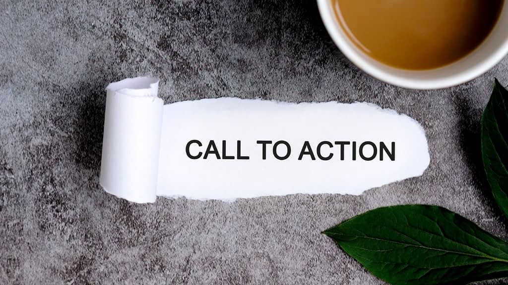 Call To Action is written on a torn peice of paper sitting on a grey desk next to a cup of coffee