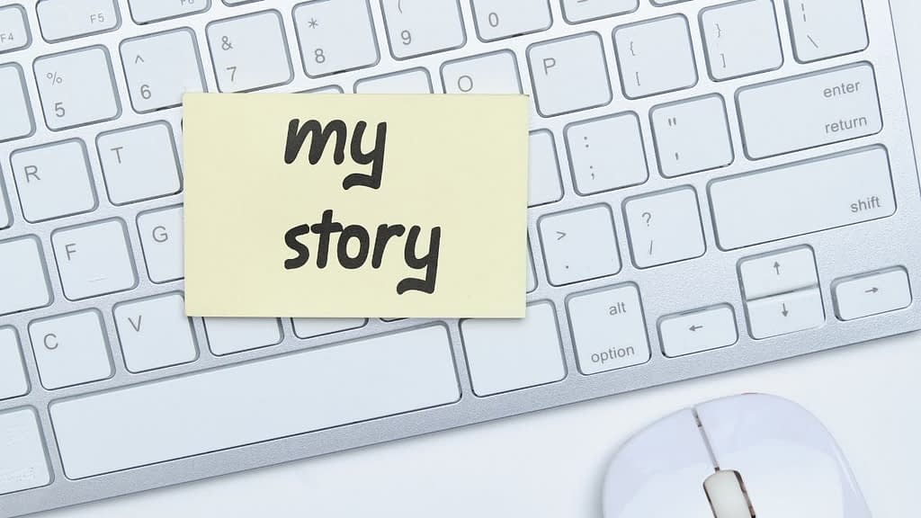 """The words """"my story"""" are written on a poste it note stuck to a computer keyboard"""