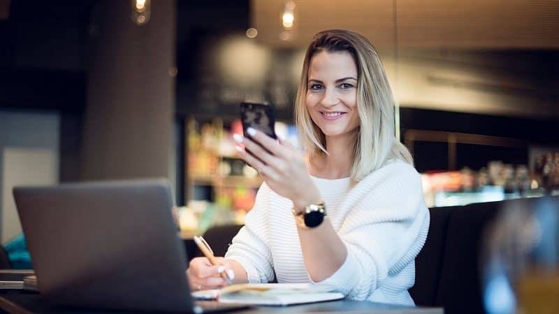 A woman is working at hme holding a cell phone and smiling. She has a laptop and is making a list of profitable niches for this year.