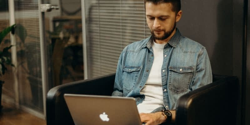 Man is sitting on his apple computer working SEO