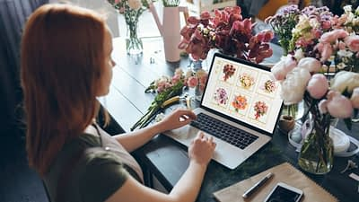 Woman sitting at a desk looking at a computer with flowers and behind her are flowers as in a flower shop.