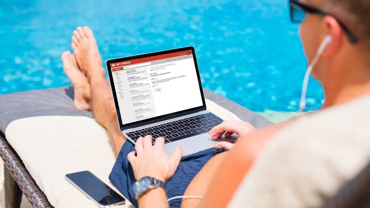 Man is by the pool with a computer on his lap and gmail open
